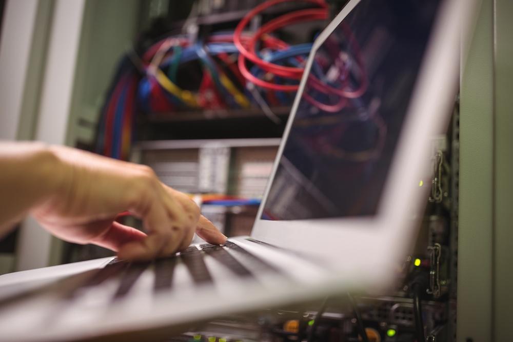 Technician working on laptop in server room.jpeg