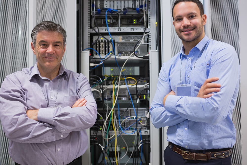 Technicians smiling while standing in front of servers in data center.jpeg